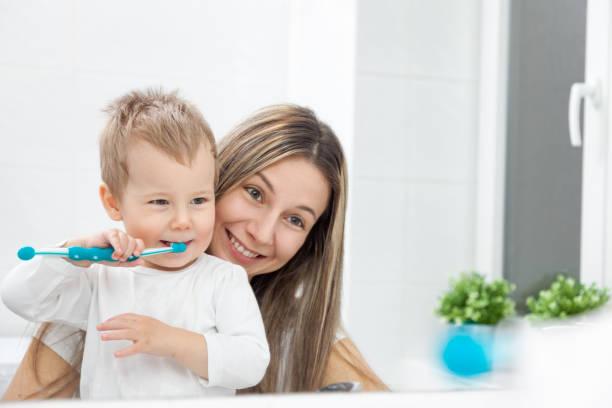 Glückliche Mutter ihren Sohn beizubringen, wie man Zähne Busch – Foto