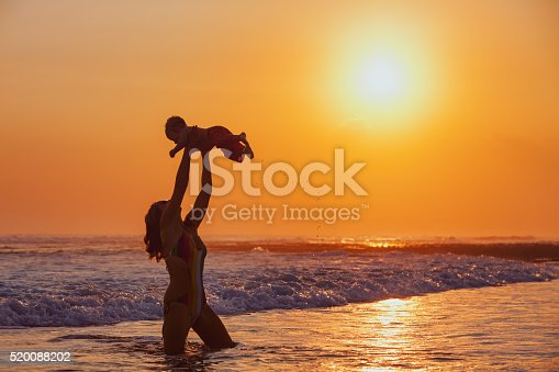 497142294 istock photo Happy mother tossing up baby son high in sunset sky 520088202