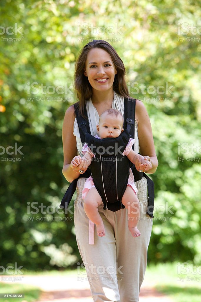 0e991fb66f2 Happy Mother Walking With Infant In Baby Carrier Stock Photo   More ...