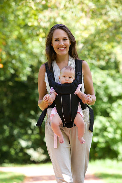 Happy mother walking with infant in baby carrier stock photo