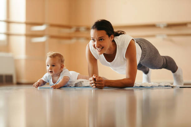 Happy mother with a baby doing plank exercise in health club. stock photo