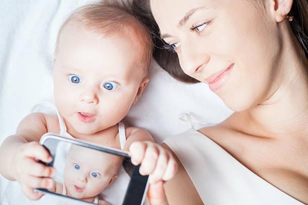 glückliche mutter mit einem baby liegen auf einem weißen bett - lustige babybilder stock-fotos und bilder