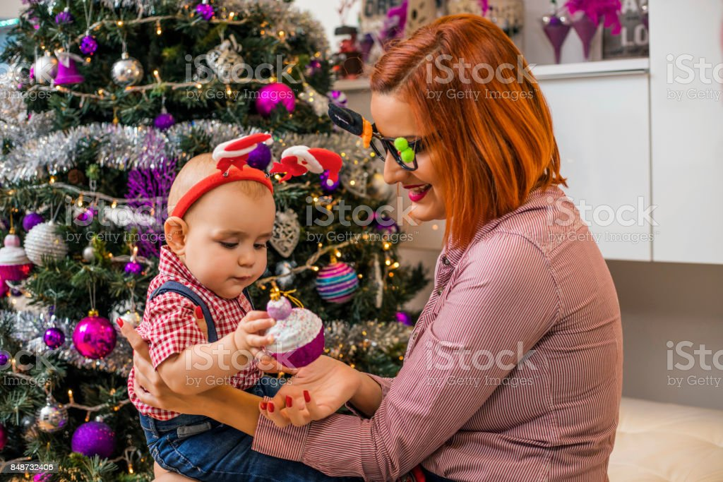 Happy mother with baby in front of Christmas tree stock photo