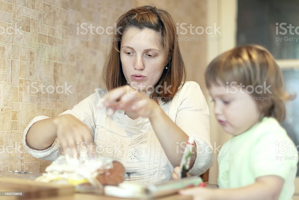 Happy mother with daughter cooking salmon in foil stock photo