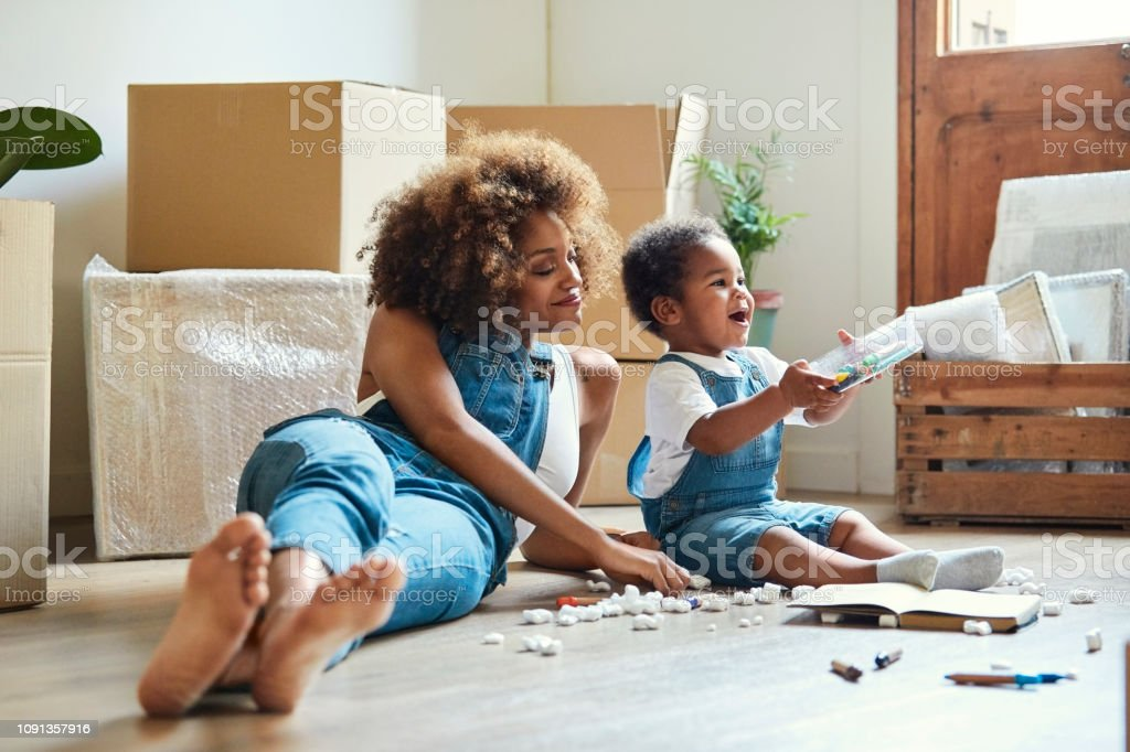 Happy mother with daughter playing in new house Happy mother reclining by daughter playing with colored pencils. Family is sitting on hardwood floor of new apartment. They are wearing bib overalls. Adult Stock Photo