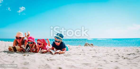 happy mother with kids reading books at beach, family on vacation at sea