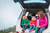 happy mother with kids travel by car on road in winter, christmas vacation