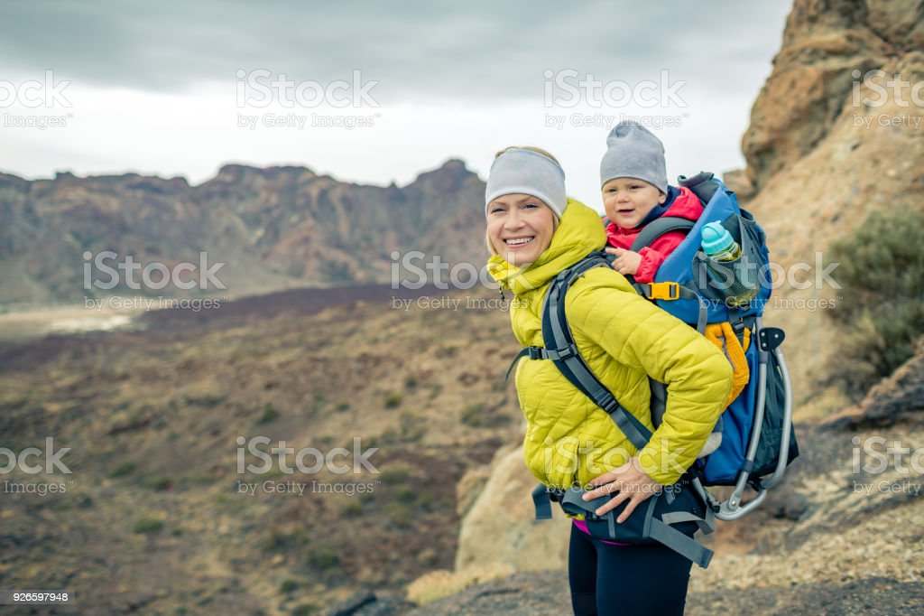 Happy mother with little boy travelling in backpack stock photo