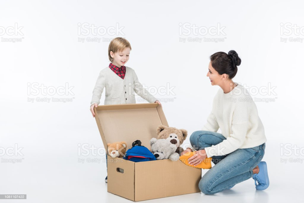 Happy mother with son sitting near cardboard box with toys isolated on white stock photo