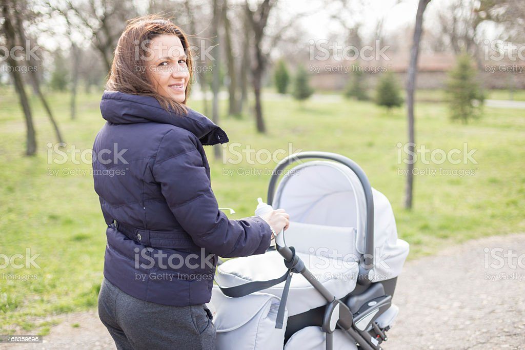 Happy mother with stroller in park royalty-free stock photo