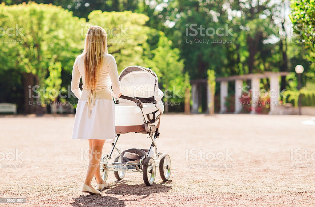 happy mother with stroller in park stock photo