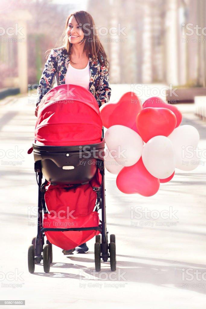 Glückliche Mutter mit Kinderwagen im park – Foto