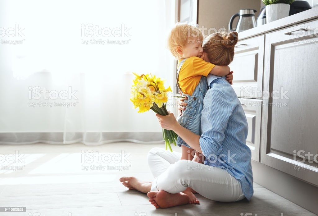 happy mother's day! baby son gives flowersfor  mother on holiday stock photo