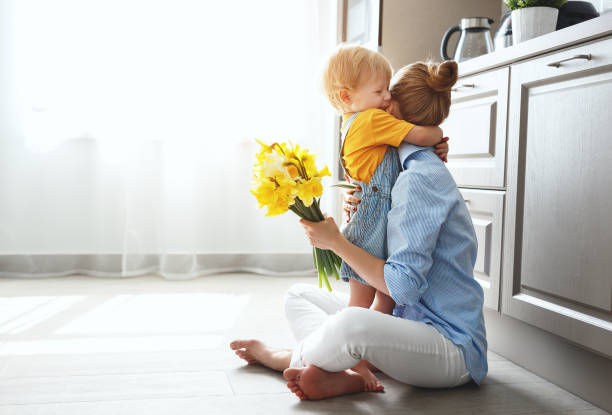 happy mother's day! baby son gives flowersfor  mother on holiday - embracing stock pictures, royalty-free photos & images