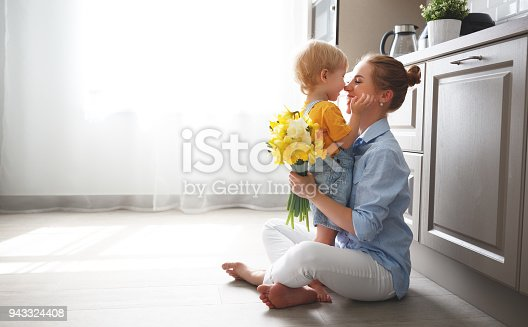 istock happy mother's day! baby son gives flowersfor  mother on holiday 943324408
