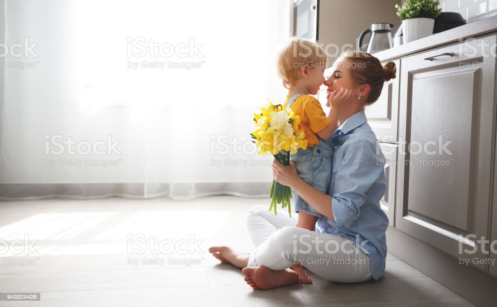 happy mother's day! baby son gives flowersfor  mother on holiday стоковое фото