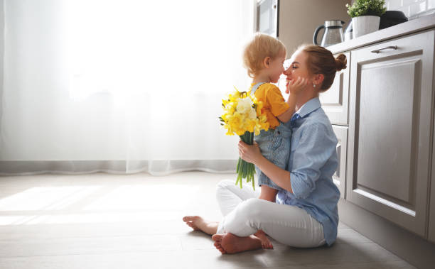 happy mother's day! baby son gives flowersfor  mother on holiday - mother stock photos and pictures