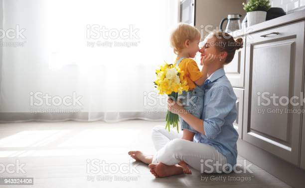 Photo of happy mother's day! baby son gives flowersfor  mother on holiday