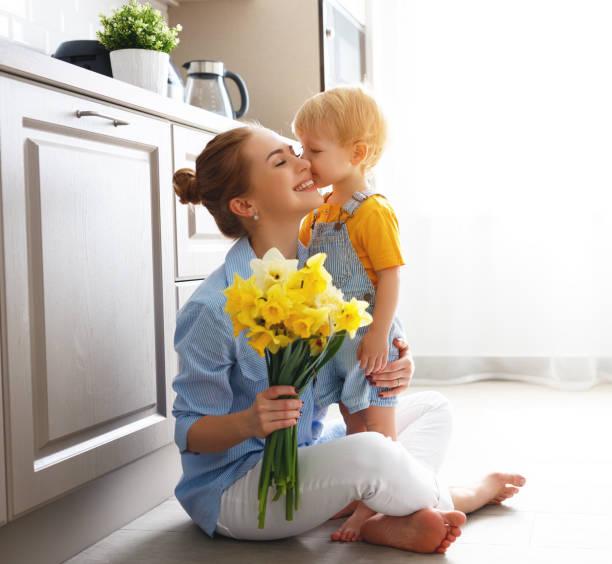 muttertag! baby sohn gibt flowersfor mutter im urlaub - alles gute zum geburtstag sohn stock-fotos und bilder