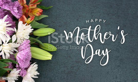 istock Happy Mother's Day calligraphy holiday script over dark blackboard background with beautiful colorful white, pink, orange, purple and green flower blossom bouquet 940292520