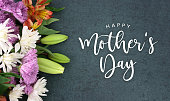 Happy Mother's Day calligraphy holiday script over dark blackboard background with beautiful colorful white, pink, orange, purple and green flower blossom bouquet
