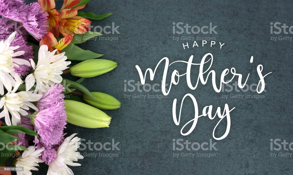 Happy Mother's Day calligraphy holiday script over dark blackboard background with beautiful colorful white, pink, orange, purple and green flower blossom bouquet stock photo