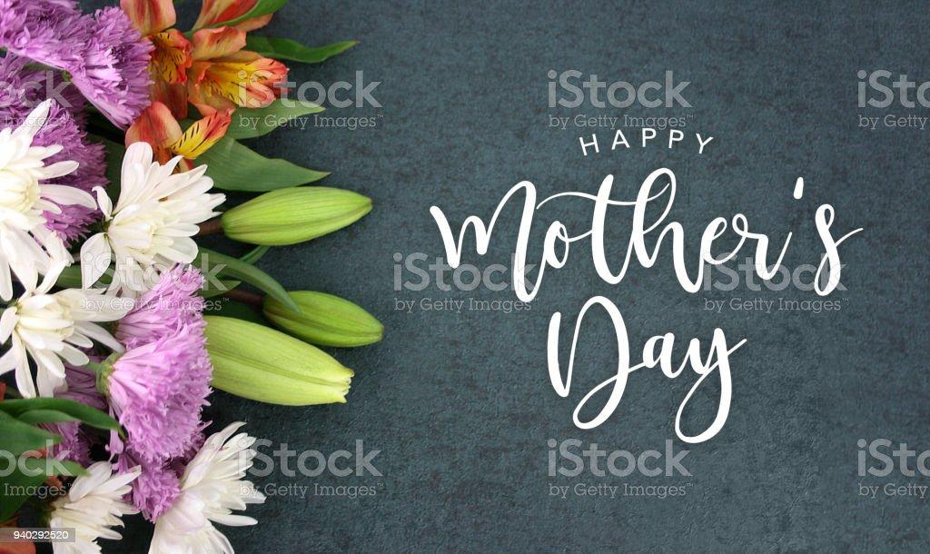 Glücklich Muttertag Kalligraphie Urlaub Skript über dunkle Tafel Hintergrund mit bunten weiß, rosa, orange, lila und grüne Blume Blüte bouquet – Foto