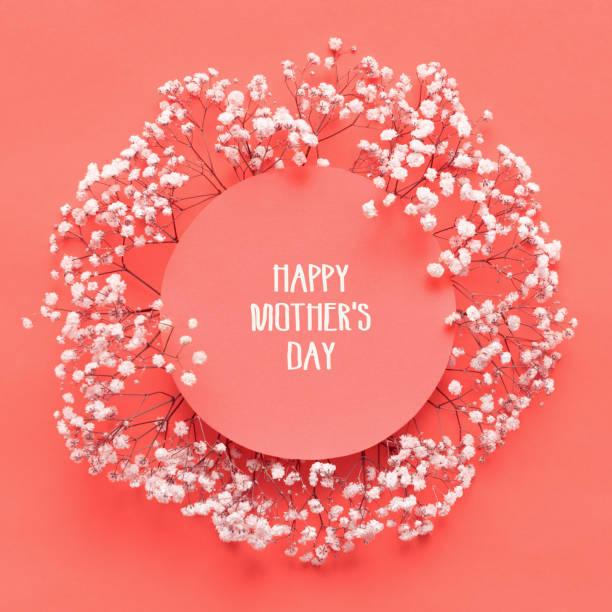 Glückliche Mütter Tag Card flach legen Grußkarte mit schönen kleinen weißen Blüten auf lebenden Korallen Pantone Farbe Papierhintergrund. – Foto