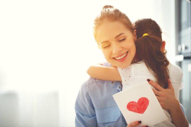 Muttertag! Kind-Tochter gratuliert Mütter und gibt ihr eine Postkarte – Foto