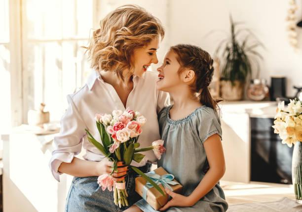 Schönen Muttertag! Kind Tochter gibt Blumen für Mutter im Urlaub – Foto