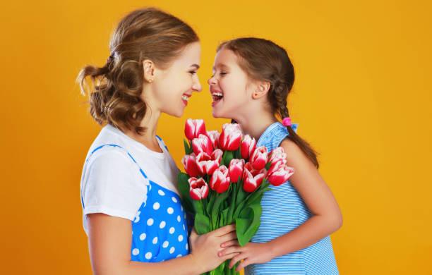 Schönen Muttertag! Kinder-Tochter gibt Mutter einen Blumenstrauß auf Farbe gelber Hintergrund – Foto