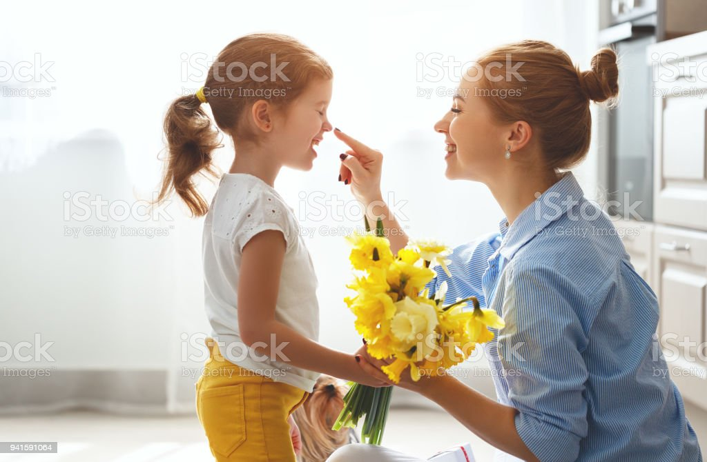 Muttertag! Kind Tochter gibt Mutter einen Blumenstrauß, Narzissen und Geschenk – Foto