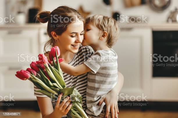 Photo of happy mother's day! child son gives flowers for  mother on holiday