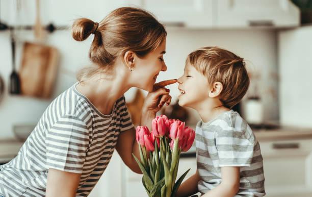 Schönen Muttertag! Kind Sohn gibt Blumen für Mutter im Urlaub – Foto