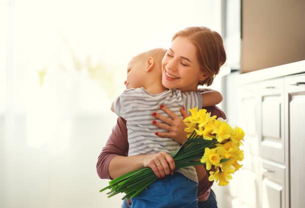 Schönen Muttertag! Kindersohn gibt Blumen für Mutter im Urlaub – Foto