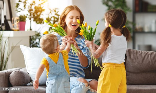 Happy mother's day! Children congratulates moms and gives her a gift and flowers tulips