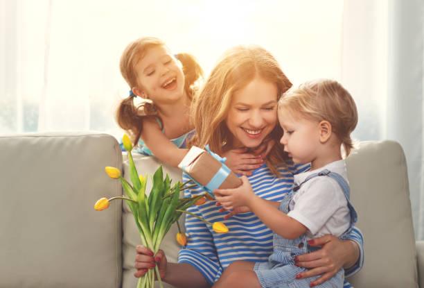 muttertag! kinder gratuliert mütter und gibt ihr ein geschenk und blumen - alles gute zum geburtstag sohn stock-fotos und bilder