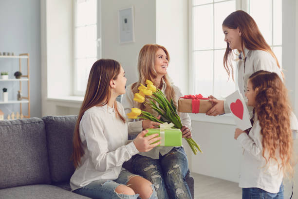 Happy Mother's Day. Children daughters give mom a bouquet of flowers at home. stock photo