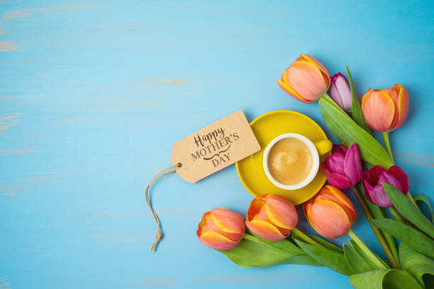 Happy Mother's day concept with coffee cup and beautiful tulip flowers on wooden background. Top view from above stock photo