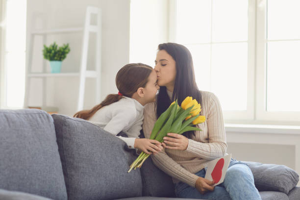 Happy mothers day. Daughter congratulates hugs his mother holds a bouquet of flowers in the room. stock photo