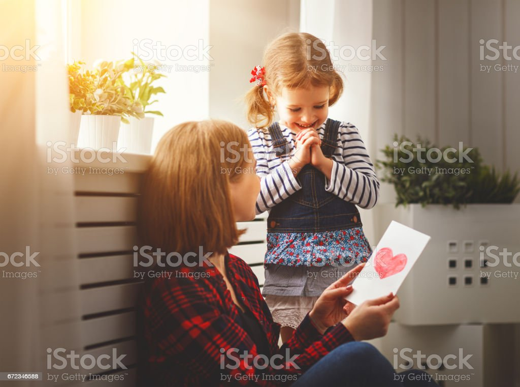 Happy mother's day! Daughter gives her mother an postcard stock photo