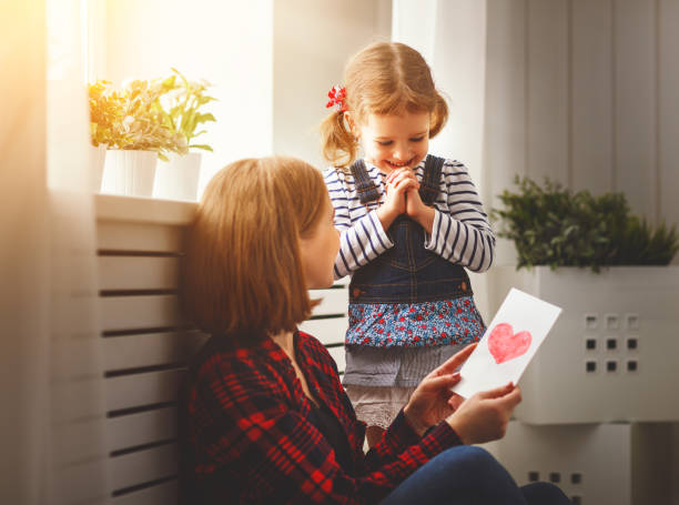 Happy mother's day! Daughter gives her mother an postcard - foto stock
