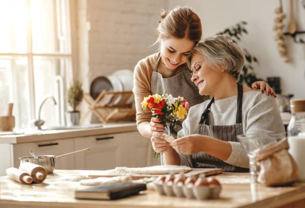 feliz día de la madre! familia vieja abuela suegra y su nuera hija felicitan en vacaciones, dar flores - hija fotografías e imágenes de stock