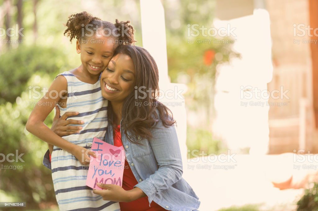 Happy Mother's Day. Girl gives card to mother. stock photo