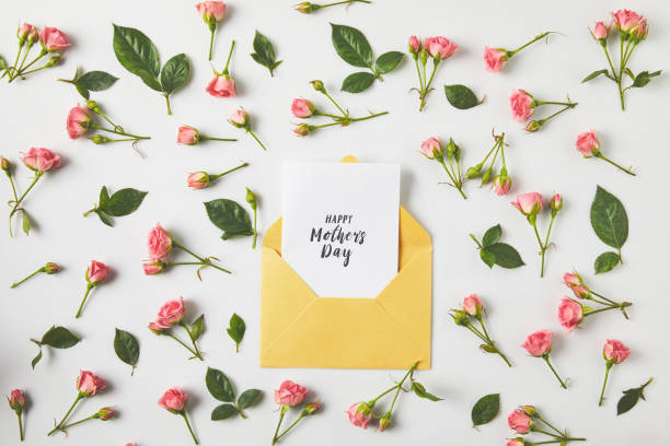 happy mothers day greeting card in envelope and beautiful pink roses and green leaves on grey - mothers day stock pictures, royalty-free photos & images