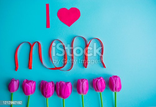 659293084 istock photo Happy Mother's day greeting card with the bouquet of beautiful spring pink tulips flowers on the light blue background. Flat lay concept. 1212992152