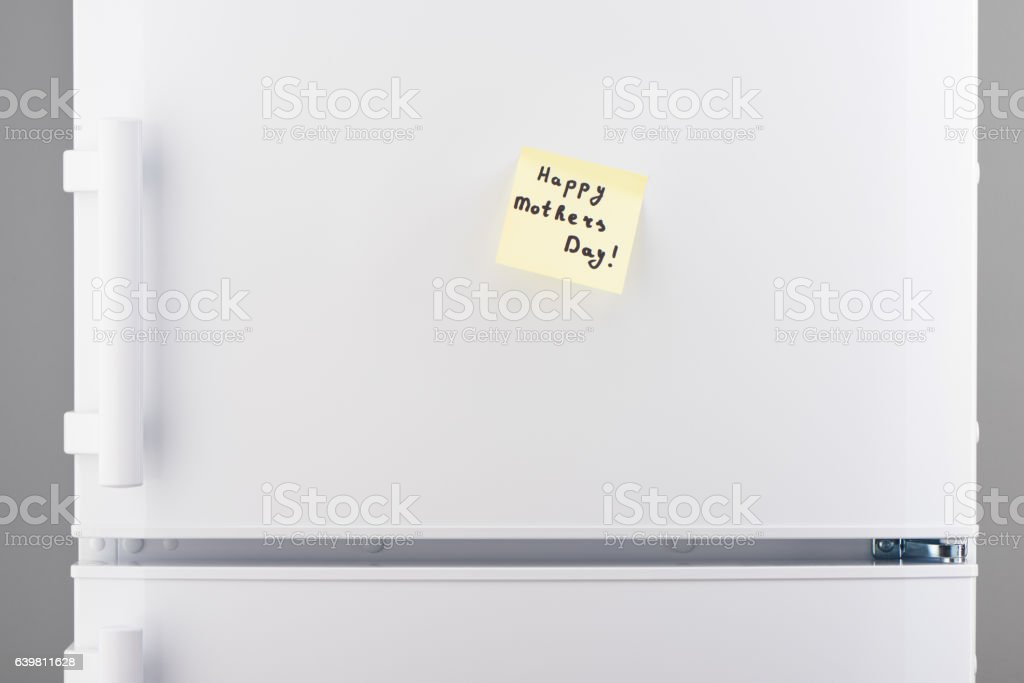 Happy Mothers Day note on yellow paper on white refrigerator stock photo