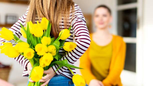 Happy Mother es Day oder Birthday Background. Entzückende junge Mädchen überraschte ihre Mutter mit Strauß von gelben Tulpen. Familienfeier Konzept. – Foto
