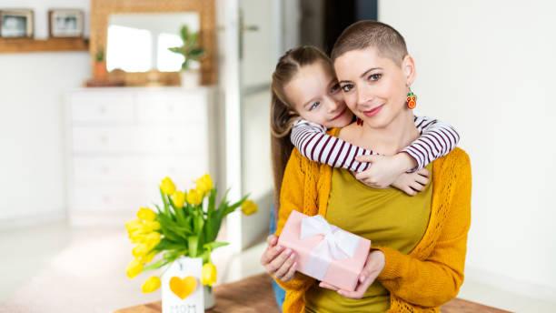 Happy Mother es Day oder Birthday Background. Entzückende junge Mädchen überraschte ihre Mutter, junge Krebspatientin, mit Blumenstrauß mit Präsent. Familienfeier Konzept. – Foto