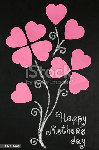 Flowers of paper hearts  and text happy  Mother's day on blackboard